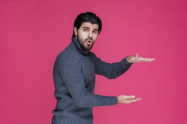개체의 측정 값을 보여주는 회색 스웨터에 남자.