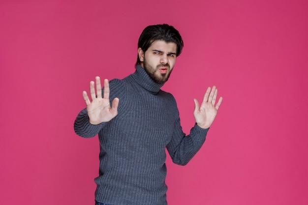 회색 스웨터를 입은 남자가 무언가를 멈추거나 예방하려고합니다.