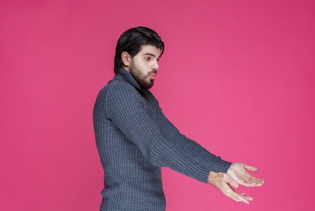 Мужчина в сером свитере с открытыми руками выглядит неопытным.