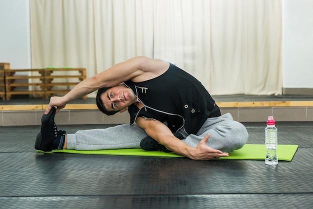 床に座ってストレッチ体操をしているジムの男