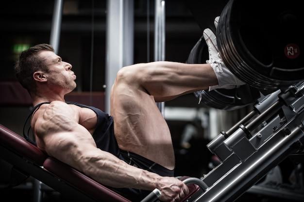 上肢の筋肉を定義するためにレッグプレスでジムトレーニングをしている男性