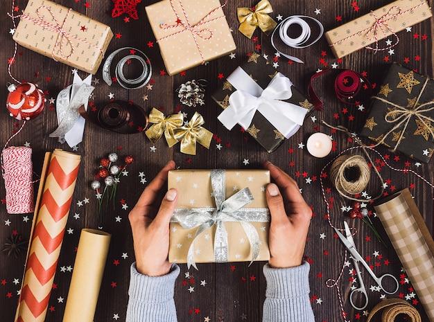 Мужчина в руке держит новогоднюю подарочную коробку