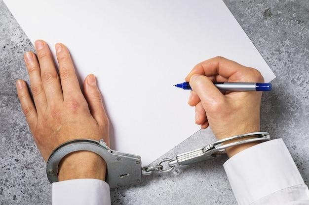 Мужчина в наручниках подписывает концепцию бланка на тему соглашения под воздействием давления на людей