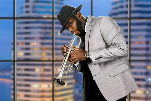 Человек в шляпе играет на трубе.