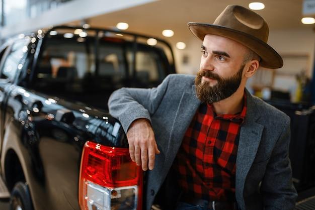 帽子をかぶった男が自動車販売店の新しいピックアップトラックでポーズをとる。