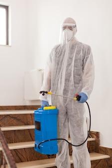 化学防護服を着た男性が、建物の階段をコロナウイルスから消毒します。