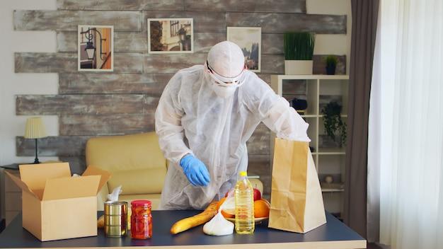 코로나바이러스 발병 동안 음식을 포장하는 방호복을 입은 남자.