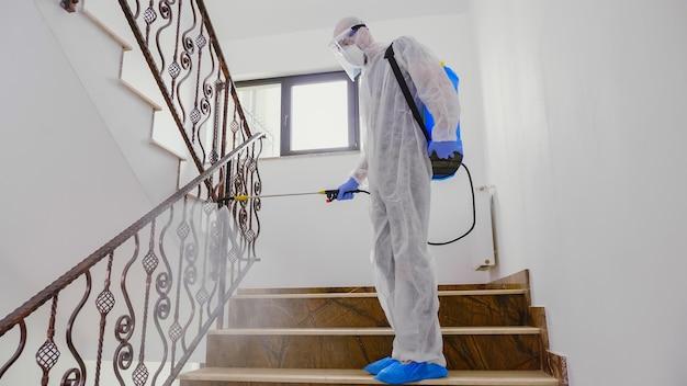Мужчина в костюме hazmat распыляет химикат на лестнице здания против распространения коронавируса.
