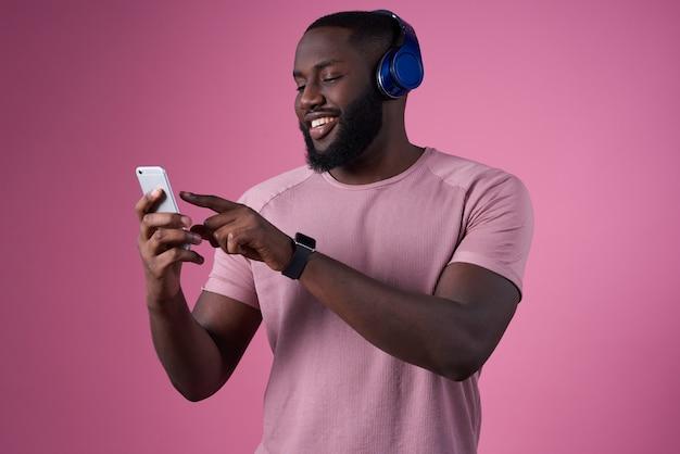 ヘッドフォンと彼の手に携帯電話を持つ男が音楽を切り替えます