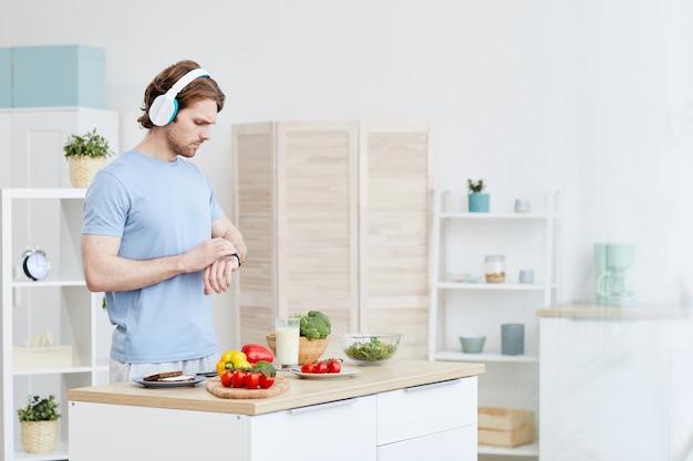 家庭の台所に立っている間、彼の時計で時間をチェックするヘッドフォンの男。彼は夕食を作るつもりです
