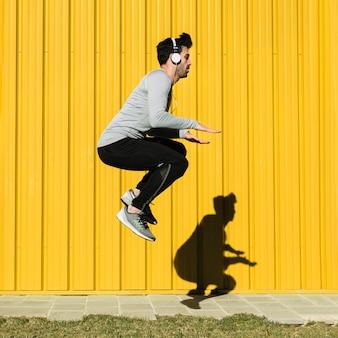 Man in headphones jumping near yellow wall