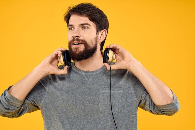 Человек в наушниках слушает музыкальные технологии, образ жизни, веселые люди на желтом фоне. фото высокого качества