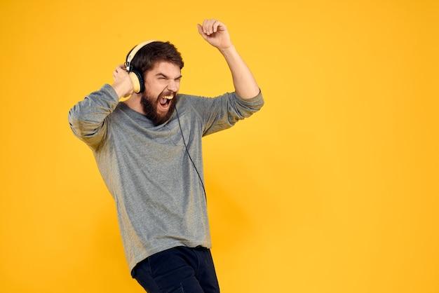 ヘッドフォンの男が黄色の音楽技術ライフスタイルの楽しい人々に耳を傾ける