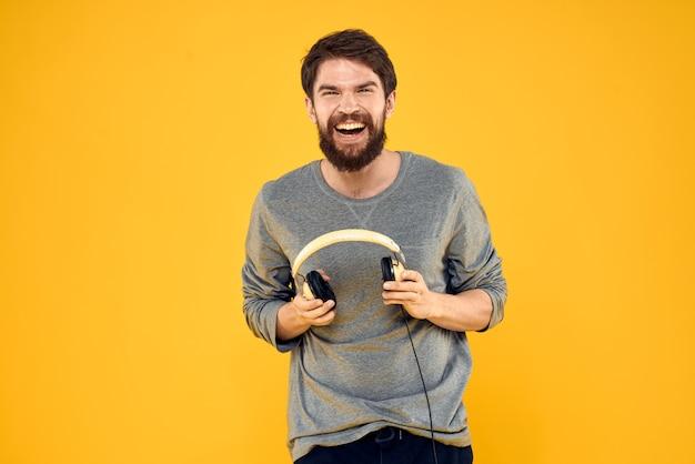 Человек в наушниках слушает музыку, технологии, образ жизни, веселье, люди, желтый