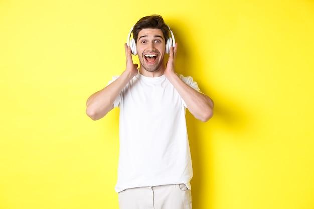 헤드폰을 끼고 놀라고 행복해 보이는 남자, 멋진 노래를 듣고 노란색 배경 위에 서 있습니다.
