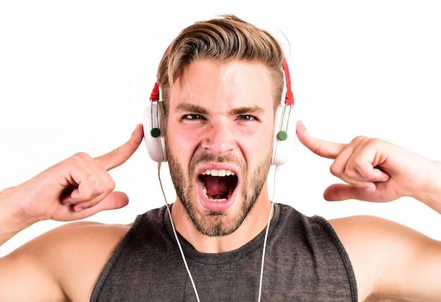 헤드폰에 남자입니다. 릴렉스 플레이리스트. 섹시한 근육질의 남자는 재생 목록에서 음악을 듣습니다. 남자는 흰색 절연 이어폰에서 휴식을 취하십시오. 면도하지 않은 남자는 좋아하는 노래로 휴식을 취합니다.