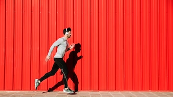 Man in headphones running near red walll
