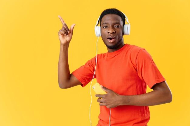 黄色の背景に彼の手で携帯電話とヘッドフォンの男