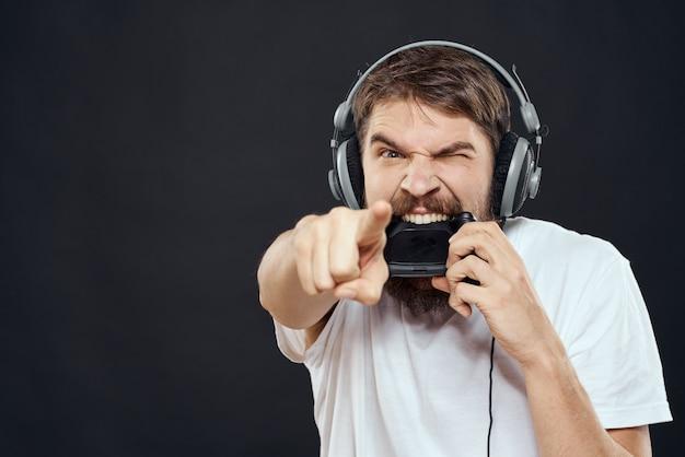 게임 패드 재미 엔터테인먼트 게임 라이프 스타일 어두운 벽 헤드폰에 남자.