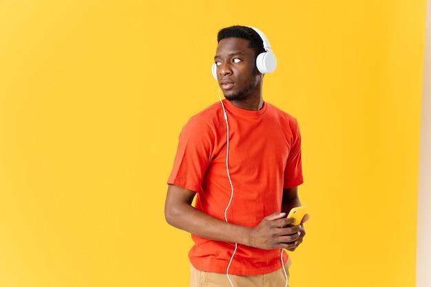 音楽エンターテインメントを聞いている手に携帯電話とヘッドフォンで男