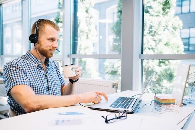 Человек в гарнитуру, работающий на ноутбуке