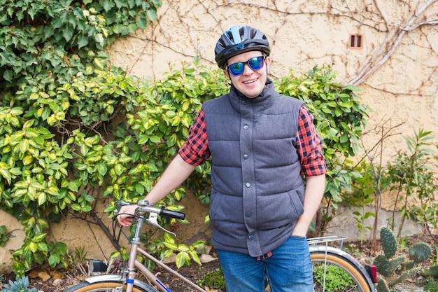 ヘルメットと眼鏡をかけた男が庭の自転車にとどまる Premium写真