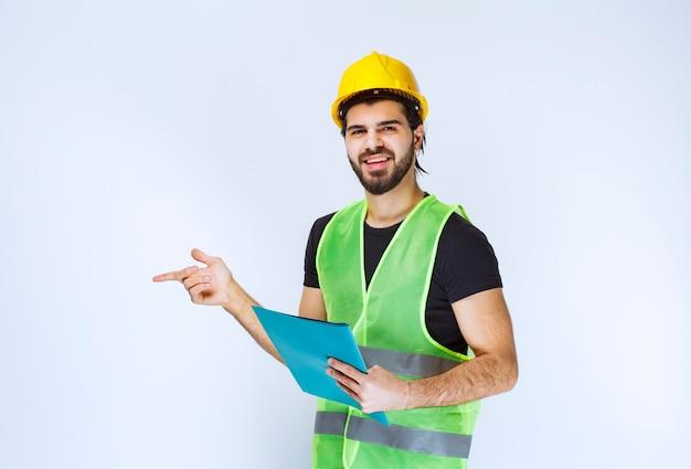 헬멧을 쓴 남자가 파란색 폴더를 들고 왼쪽에 있는 누군가를 가리키고 있습니다.