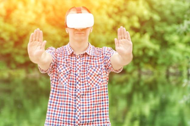 Человек в шлеме виртуальной реальности на фоне природы.