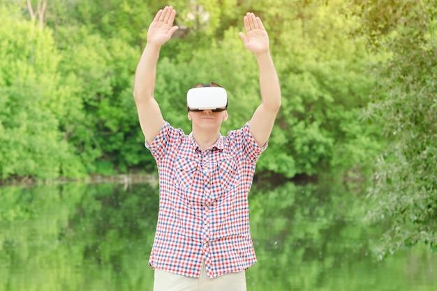 自然に対する仮想現実のヘルメットをかぶった男。手を挙げて