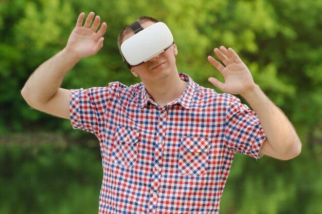 自然の壁に対する仮想現実のヘルメットをかぶった男。手を挙げて