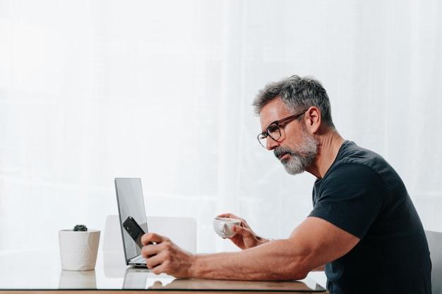 전화와 컴퓨터 메시지를 받으며 재택근무를 하는 50대 남성