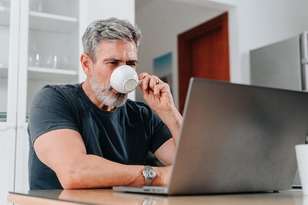 50대 남성이 집에서 커피를 마시며 컴퓨터로 영상통화를 하고 있다