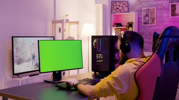 그의 방에 있는 남자는 녹색 화면이 있는 컴퓨터에서 비디오 게임을 하며 휴식을 취합니다. 게임의 자에 앉아 남자입니다.