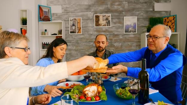 家族の夕食でパンを妻に提供する60代の男性。