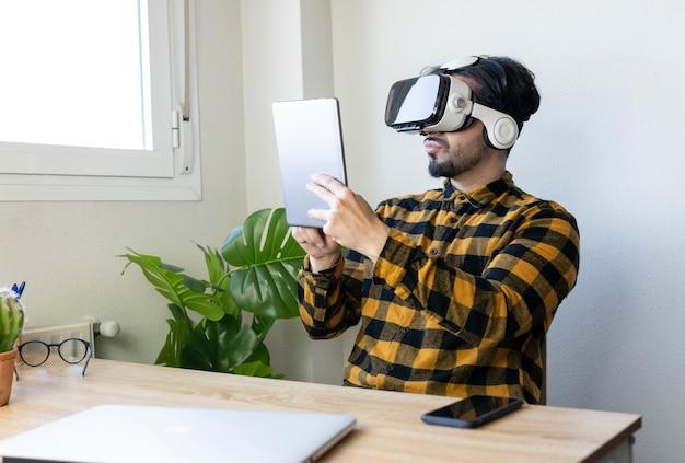 ホームオフィスの男性は、バーチャルリアリティメガネとタブレットで動作します