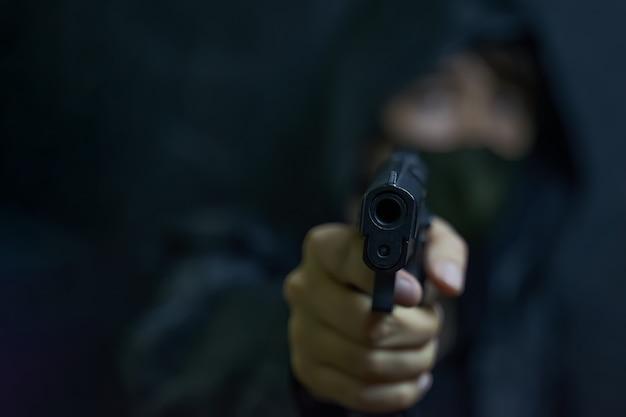 후드와 마스크를 쓴 남자가 살인자나 무장한 도둑 범죄를 저지르는 총기 리볼버로 위협합니다...