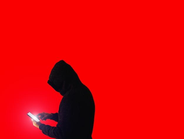 パーカーを着た男が個人データをハッキングしています。情報セキュリティー。情報の概念の保護。不正なパスワード。