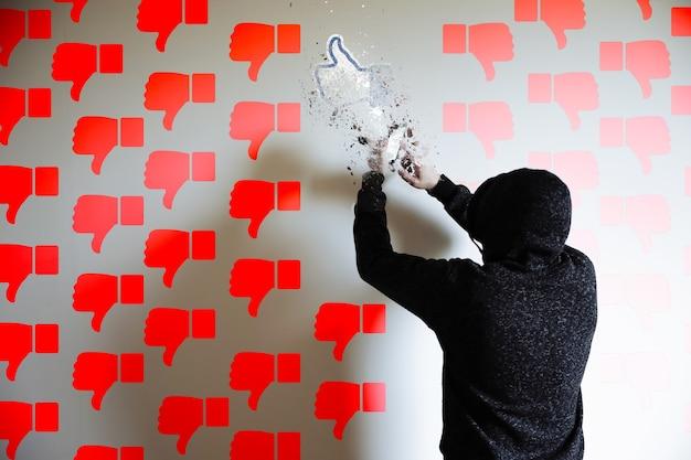까마귀를 입은 남자가 전화를 찾고 있습니다. 빨간색은 싫어합니다. 소셜 네트워킹 중독. 가상 통신. 정보 보안.