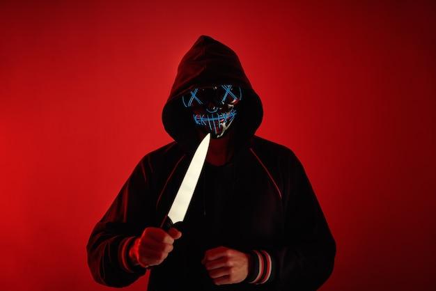 Человек в толстовке с пугающей маской на лице держит нож в руке