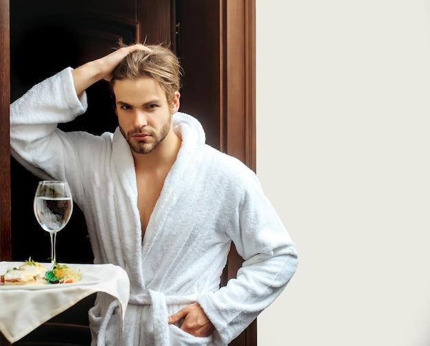ホテルの男若いハンサムな男白いテリー織りのバスローブでホテルのウェイターの人間の手の近くに食べ物と水ガラスのトレイ
