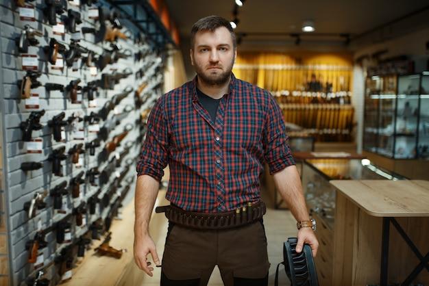 狩猟服の男が銃専門店で弾薬帯を保持