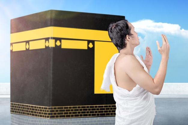 Человек в одежде ихрама стоит и молится на фоне каабы и голубого неба