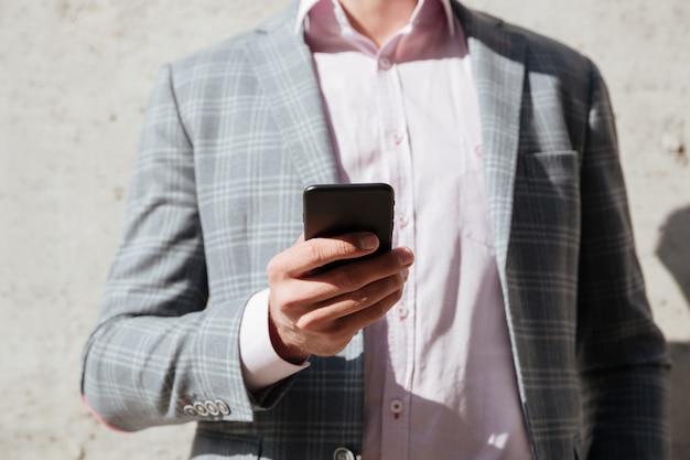 Мужчина в куртке держит мобильный телефон