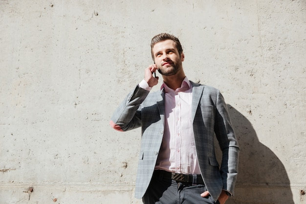 Человек в куртке разговаривает по мобильному телефону и смотрит вверх