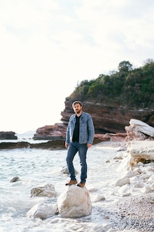 청바지에 남자와 데님 재킷은 조약돌 해변에 큰 돌에 선다