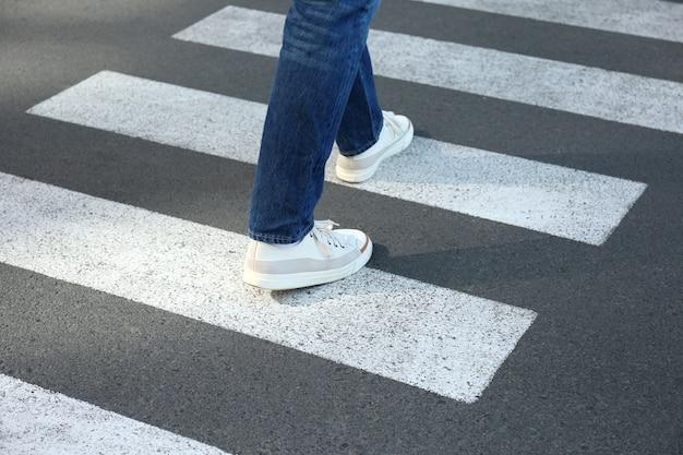 Человек в джинсах и кроссовках идет по пешеходному переходу.