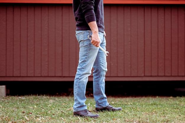 レンチを持っているジーンズの男
