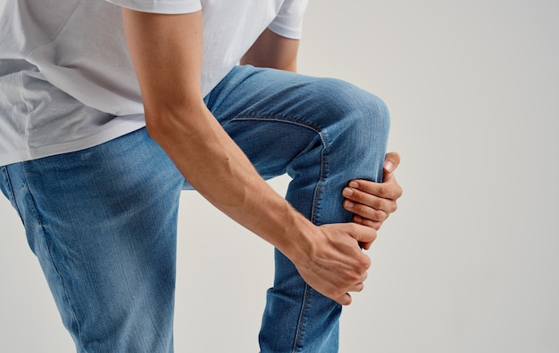 Мужчина в джинсах касается колена руками на светлом фоне.