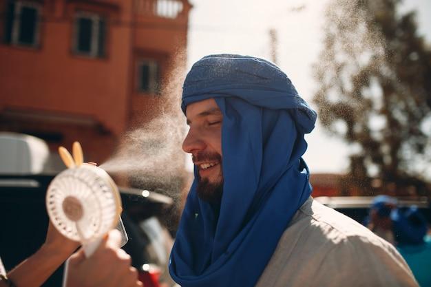 Человек в куфия с вентилятором и брызг воды. парень наслаждается теплом