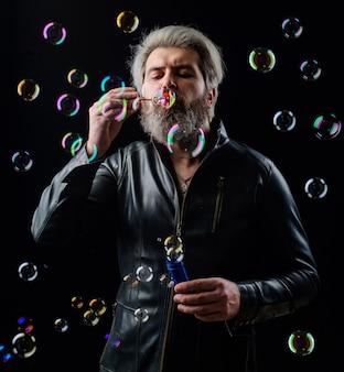 シャボン玉を吹く革のジャケットの男。幸せ。良い雰囲気。子供の頃の概念。あごひげを生やした男は泡で遊ぶ。